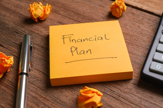A memo notes written with financial plan with pen and calculator beside over a wooden board