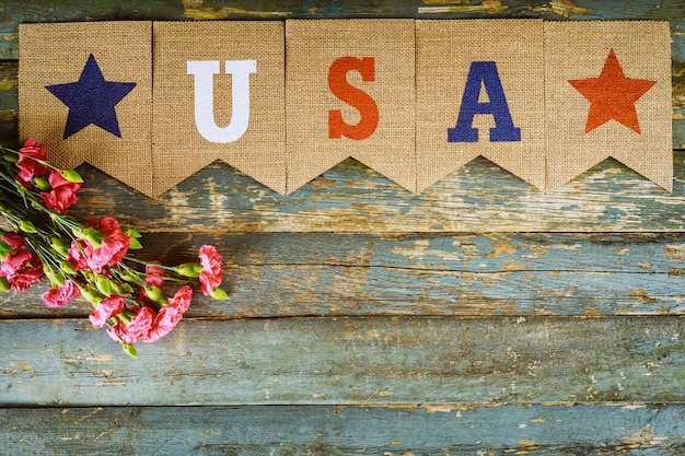 Memorial day, veterans celebration with text usa on pink carnation flowers
