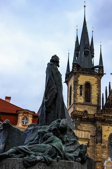 Memorial jan hus looked at the tower of the týn church from behind on a cloudy day in prague.
