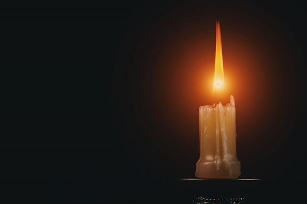 Memorial shot of one candle flame on black background