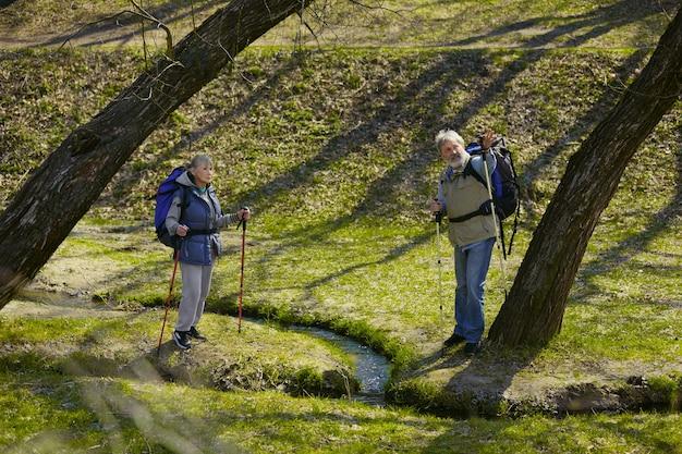 幸せの思い出。小川の近くの晴れた日に緑の芝生で歩く観光服の男性と女性の老家族カップル