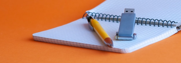 知識の記憶:本と手帳がテーブルの上にあり、ストレージデバイスとボールペンがノートブックに置かれています。これはデータを記録および保存するための新しいテクノロジーです。