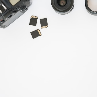 Memory cards; camera lens and professional dslr digital camera on white background