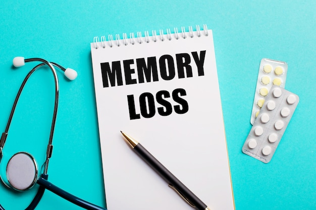Memory loss written in a white notepad near a stethoscope, pens and pills on a light blue background. medical concept