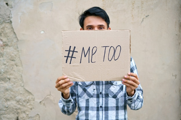 Men alone with depressed expression and showing a paper with a metoo text metoo as a new movement id...