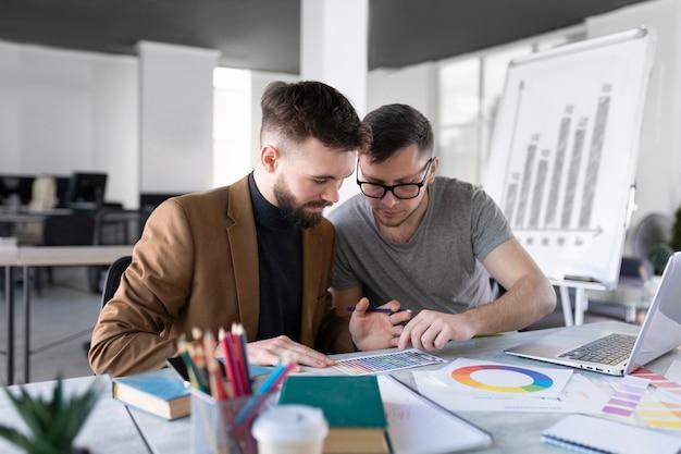 Мужчины анализируют график вместе на работе