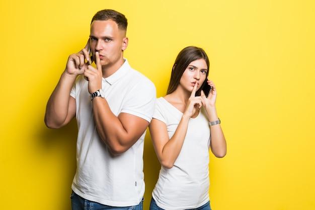 男性と女の子は黄色で隔離された彼らの携帯電話で話している間静かにしてください