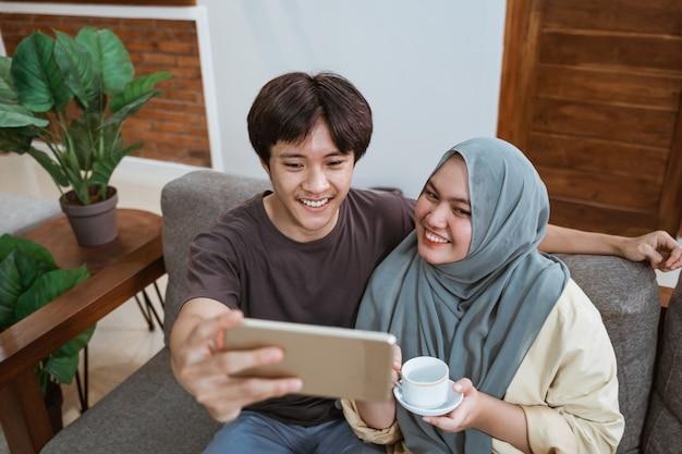 히잡을 입은 남자와 여자는 거실에 앉아 컵을 들고 웃고 셀카를 찍으면서 스마트 폰 화면을 봅니다.