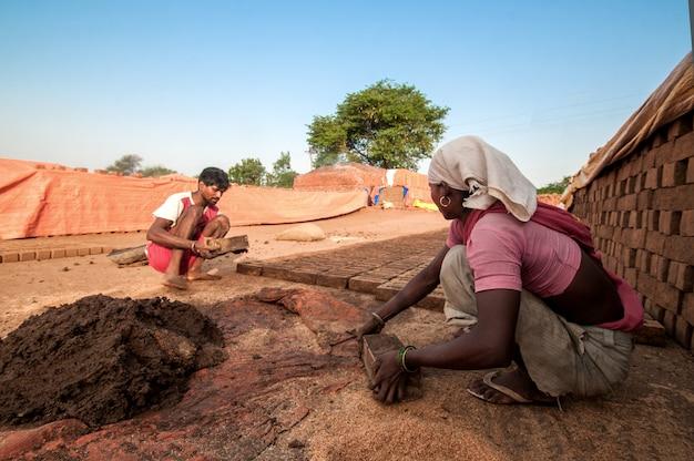 レンガ工場で伝統的なレンガのレンガを作る男女