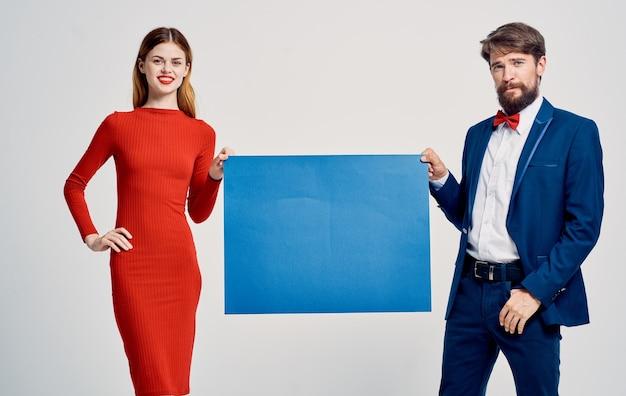 男性と女性は紙のポスターのモックアップの青いシートを保持しています。高品質の写真