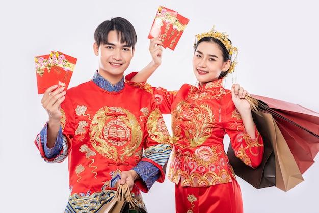 남성과 여성은 빨간 봉투로 쇼핑하러 종이 봉지를 들고