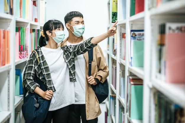 Мужчины и женщины несут рюкзак и ищут книги в библиотеке.