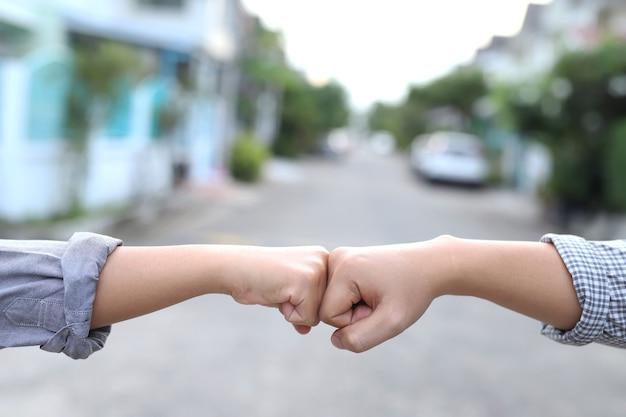 Мужчины и женщины здороваются друг с другом, не пожимая руки, чтобы предотвратить заражение вирусом.