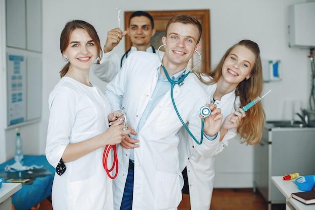 病院のガウンの男性と女性は、医療機器を手に持っています