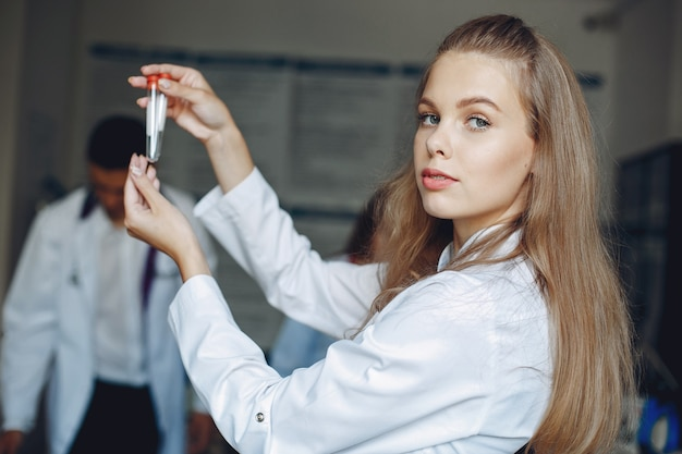 병원 가운을 입은 남녀가 연구합니다. 테스트 튜브와 간호사.