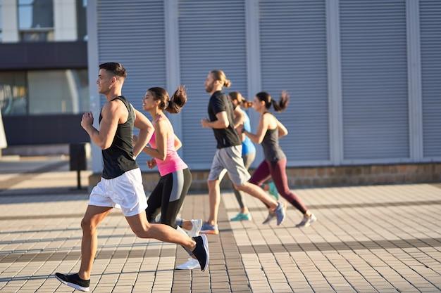 Мужчины и женщины в спортивной одежде бегают трусцой на открытом воздухе