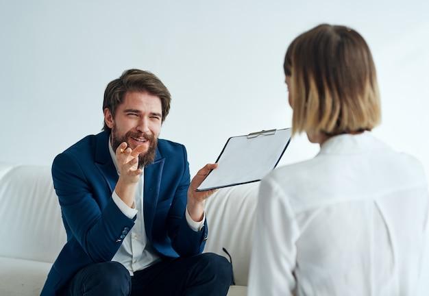 Мужчины и женщины в костюмах коллег на работе в офисе общаются