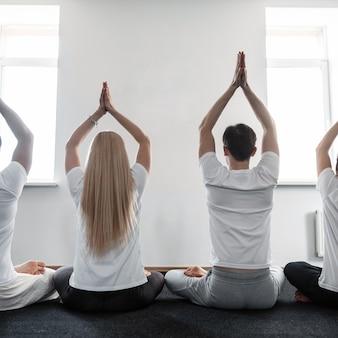 남자와 여자는 요가 수업에 대해 명상합니다. 사람들의 그룹은 스트레칭 훈련에서 하는 것을 좋아합니다.