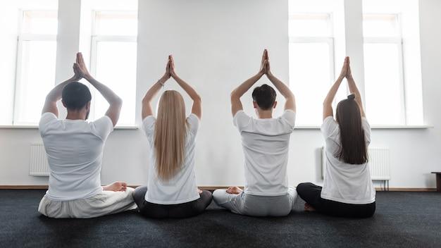 남자와 여자는 요가 수업에 대해 명상합니다. 스포티한 사람들의 그룹은 스트레칭 훈련을 하는 것을 좋아합니다.