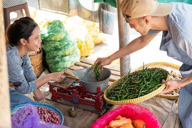 Мужчины и женщины, продающие овощи, взвешивают зеленый перец чили и несут поднос с зеленым перцем чили на традиционном рынке