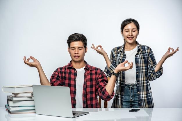 男性と女性はオフィスでラップトップを使用し、手のサインを大丈夫にします。