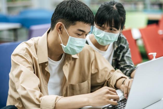 남자와 여자는 마스크를 쓰고 랩톱을 사용하여 도서관에서 책을 검색합니다.