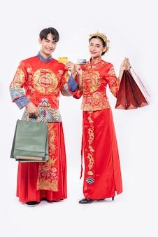 男性と女性はチャイナドレスを着て、紙袋を持って、クレジットカードで買い物に行きます。