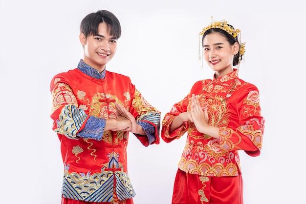 남성과 여성은 경의를 표하기 위해 qipao를 착용합니다. 흰색 배경에 고립