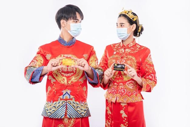 チャイナドレスとフェイスマスクを身に着けている男性と女性は、クレジットカードで買い物に行きます。