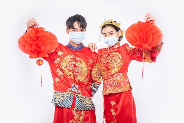 チャイナドレスとフェイスマスクを着用した男性と女性ハニカムランプ付きスタンド