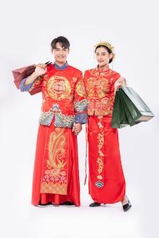 Qipao를 입은 남녀는 종이 봉투를 들고 쇼핑을합니다.