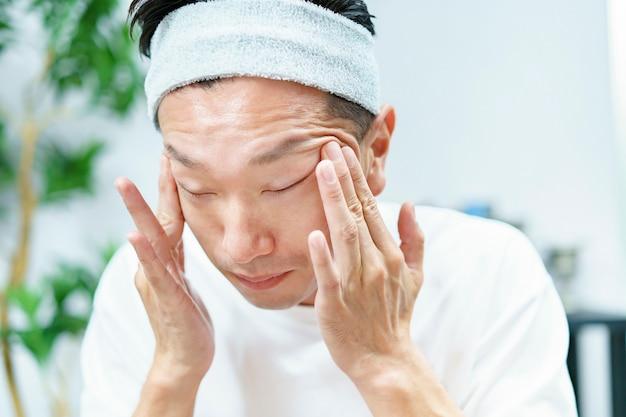 Мужчины наносят увлажняющий крем на лицо в комнате Premium Фотографии