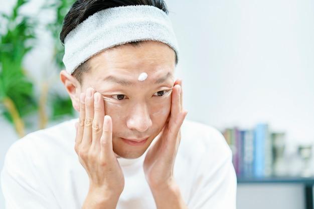 Мужчины наносят увлажняющий крем на лицо в комнате