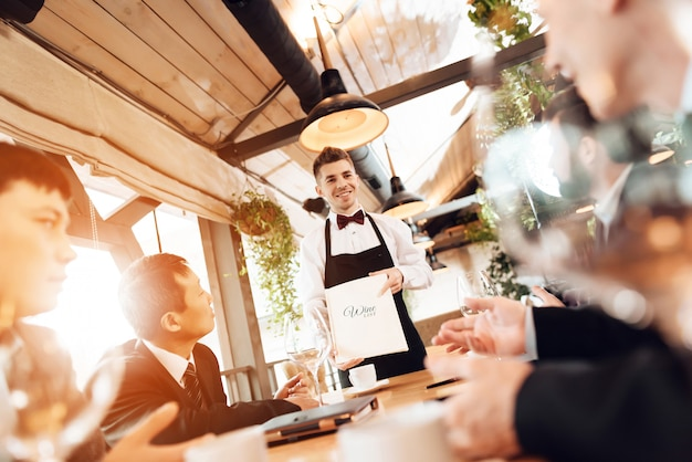 Men are choosing wine in restaurant