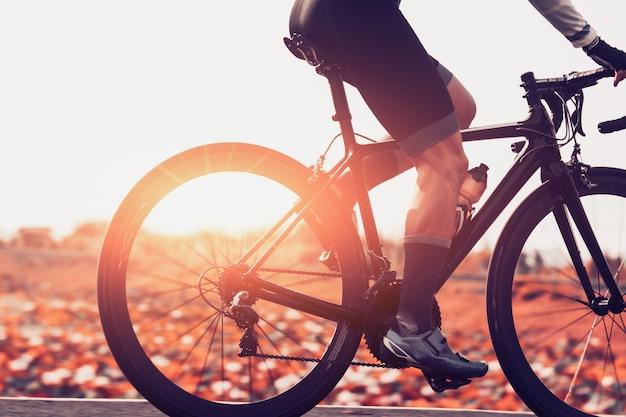 男性は日の出の道路をサイクリングしています。