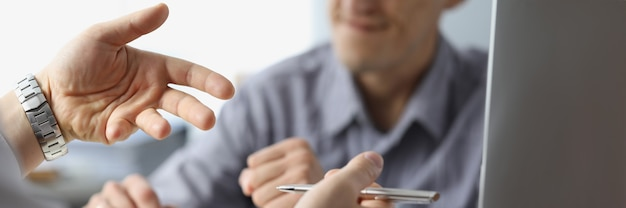 Men are discussing at table in office and gesturing closeup