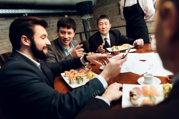 Men are eating sushi and talking.