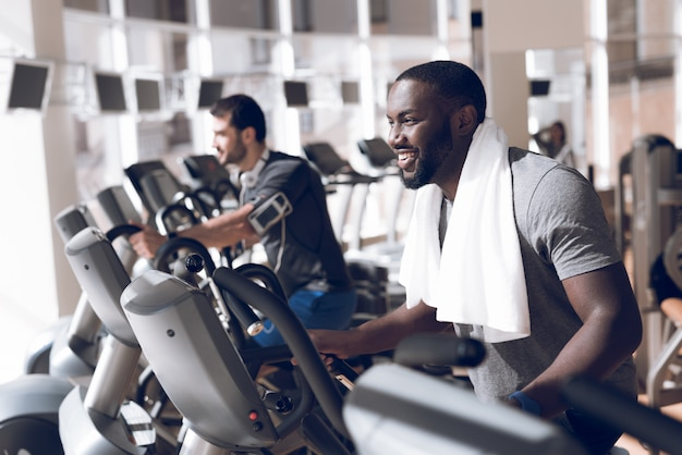 Men are engaged on the treadmills in the gym.