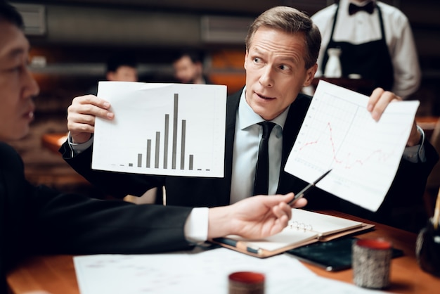 Men are looking at graphs and charts.