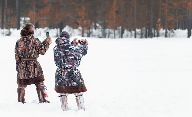 Men are photographed on phones. holiday of the day of the reindeer northern peoples