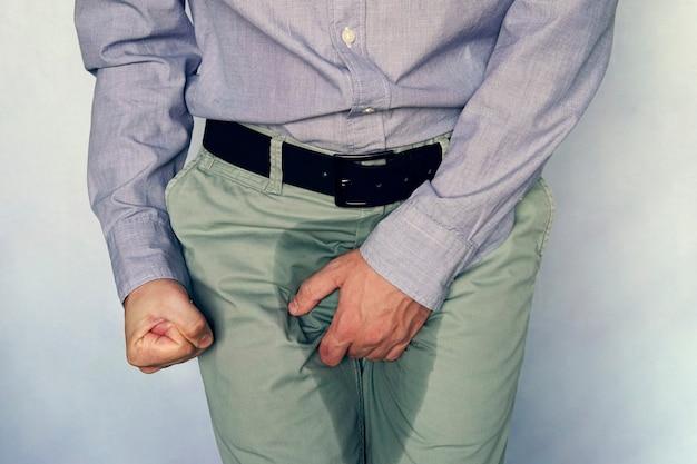 Мужчины чешут пенис на серо-голубом фоне. у людей чешется промежность. проблема человеческого тела или концепция здравоохранения и медицины. недержание мочи и мокрые штаны Premium Фотографии