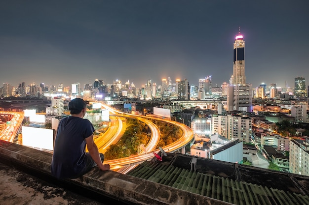 Men are sitting on balcony with sightseeing the city glowing at night