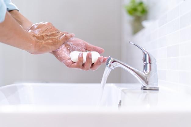男性はバスルーム内の洗面台の前に立って石鹸ときれいな水で手を洗っています。手や腕を頻繁に掃除することで、病原体やウイルスの拡散を防ぎます。