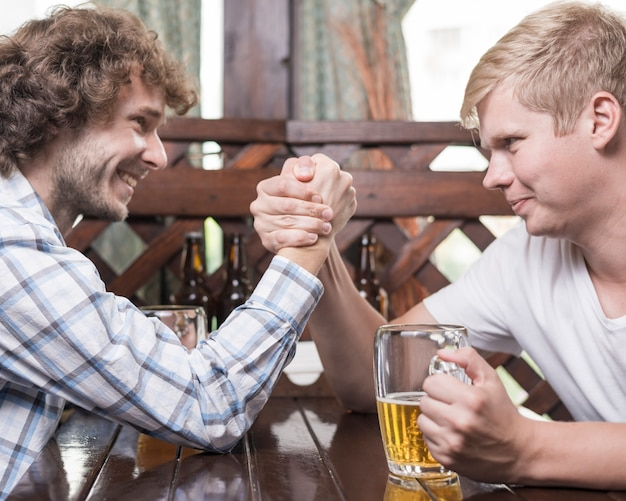 Men arm wrestling in bar