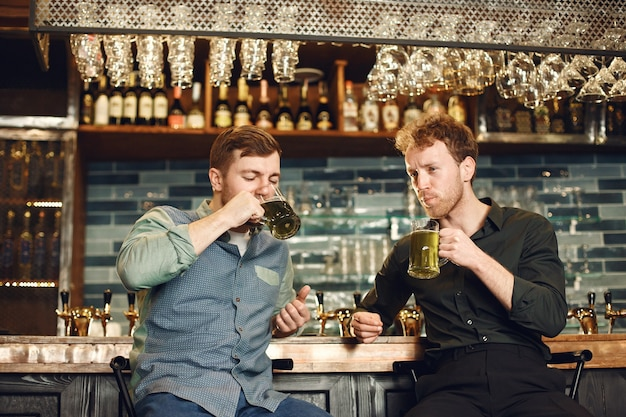 バーの男性。ビールを飲む男。男性はビールのジョッキを介して通信します。