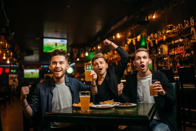 Мужчины за столом с пивом, чипсами и крекерами