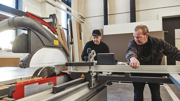 목재 원형 톱 기계를 톱질하는 직장에서 남자들은 목재 파티클 보드와 섬유판을 톱질한다