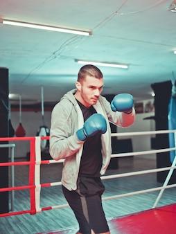 ジムでボクシングのリング内のシャドウボクシングを行う男性ボクサー。彼のパンチを練習しているボクサー