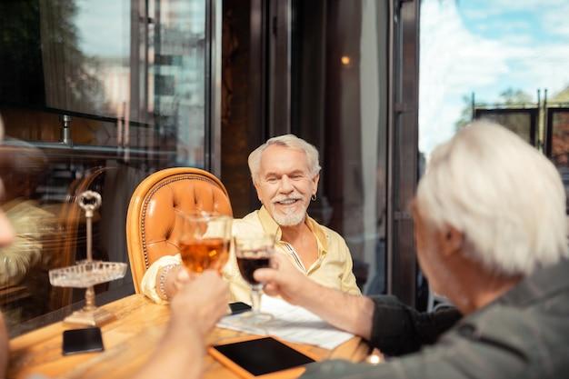축하하는 남자들. 술을 마시며 은퇴를 축하하는 은퇴한 노인들