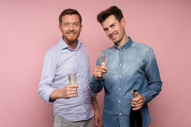 Men celebrating with champagne bottle and glasses
